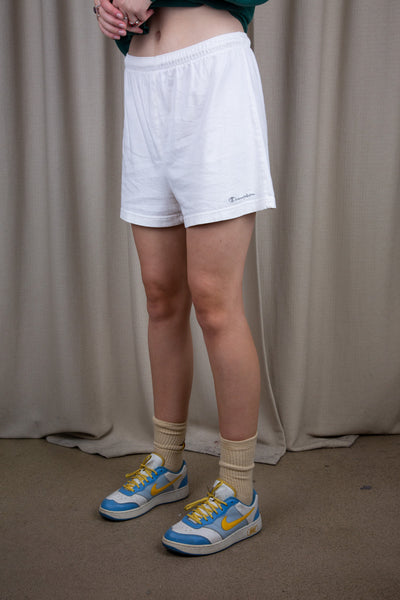 Comfy white shorts with an elasticised waistband and grey Champion branding on the left leg.