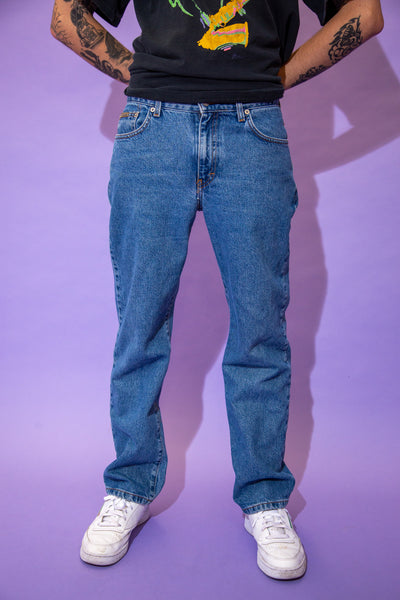 Mid-wash blue jeans in a straight leg fit with brown stitching and Calvin Klein stitching on the button, front pocket and back waistline.