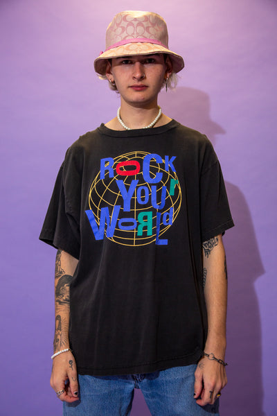 Black single stitch tee with 'Rock Your World' printed in purple over a globe print. On the back, 'Rock and Roll Hall of Fame + Museum' is printed in purple with a weird abstract print in the middle. Repping Cleveland Ohio below