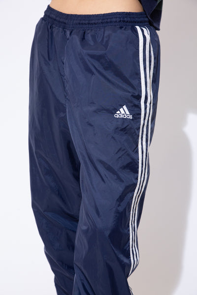 the model wears a pair of navy adidas trackpants