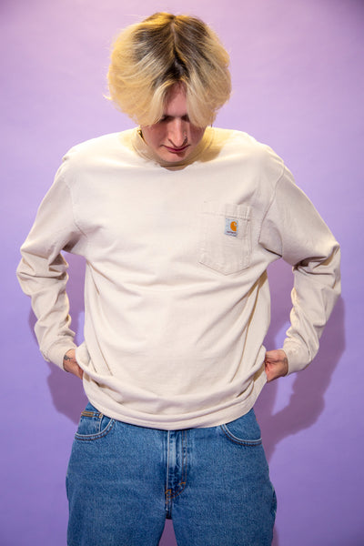 Thick, beige long-sleeved tee in a crew neck style with Carhartt branding on the left chest pocket.