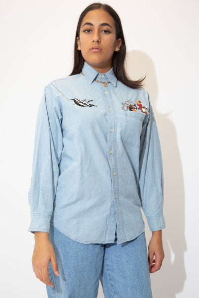 the model wears a looney tunes button up