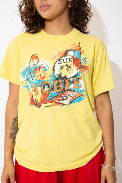 the model wears a yellow tee with hobie surf graphic