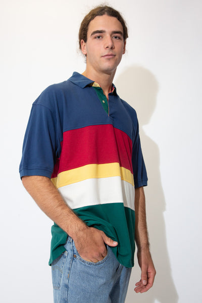 Striped in navy blue, red, yellow, white and dark green, this ribbed feel polo has cream buttons and the Tommy Hilfiger lion emblem on the left/bottom.