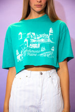 Load image into Gallery viewer, the model wears a turquoise crop with a lighthouses of maine graphic on the front