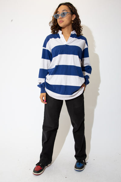 the model wears a blue and white striped rugby