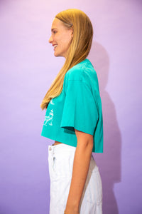 the model wears a turquoise crop with a lighthouses of maine graphic on the front