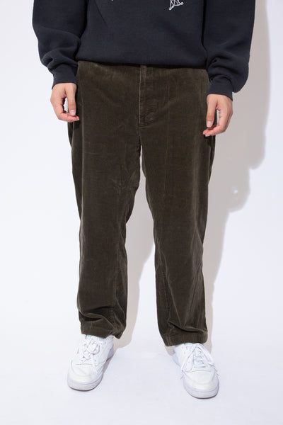 the model wears a khaki green pair of corduroy pants