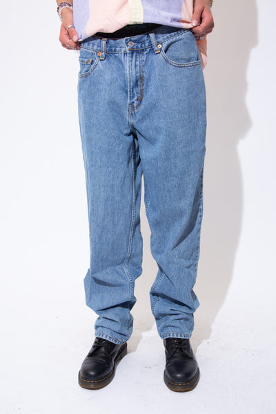 Soft mid-wash blue jeans in a straight to slightly tapered leg fit with light brown stitching, belt loops and Levi's branding on the button, domes, back waistline and back pocket.