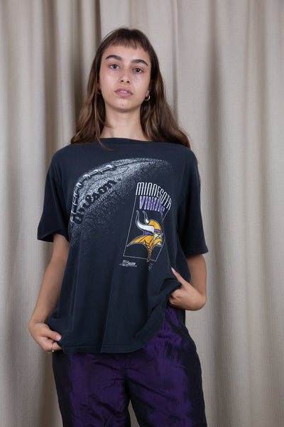 the model wears a faded black tee with a minnesota vikings graphic on the front