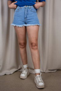 the model wears a pair of blue denim shorts