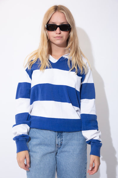 Horizontally striped in blue and white, this rugby style sweater has a white collar with matching white buttons.