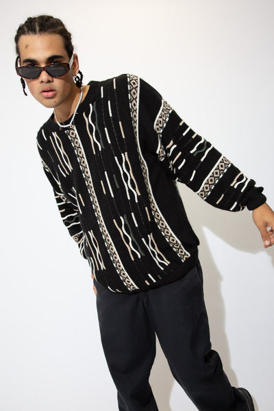 Black in colour, this knitted sweater has a cream, brown and green vertical pattern across the jumper.