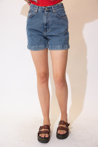 Faded mid wash denim shorts with folded bottoms, brown stitching and Calvin Klein Jeans branding on the button, front pocket and back waistline.