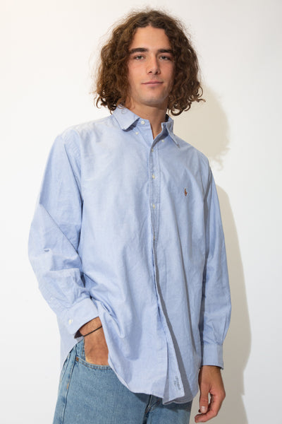 Thick light blue button-up with full-length white buttons and a colour Ralph Lauren logo embroidered on the left chest.