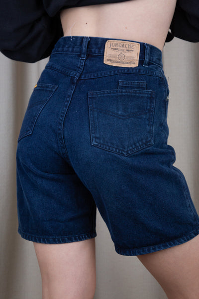 Dark-wash blue denim shorts in a midi-length fit with matching dark blue stitching and Jordache branding on the button, domes, back left pocket and back waistline.