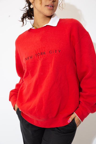 the model wears a red sweater with a nyc spell out