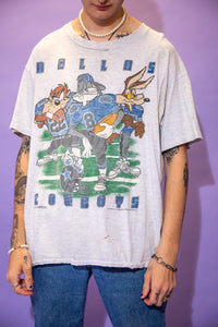 Grey in colour, this single stitch tee has a large colour print of our fav childhood gang, Bugs, Taz and Wile E in their football gear looking fly as fuck. 'Dallas Cowboys' is printed in blue with the team's logo on a football helmet below.