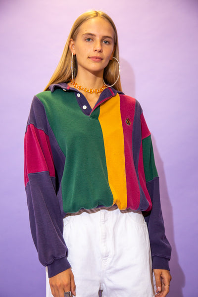 the model wears a cropped rugby with a green, yellow, red and navy