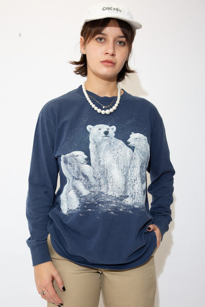 the model wears a navy longsleeve with a polar bear graphic