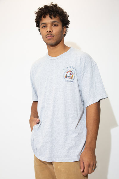 Horizontally striped in grey and white, this single stitch tee has 'St Michaels International' spell-out on the left chest with a flag and boat print.