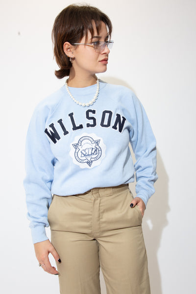 the model wears a baby blue sweater with a wilson spell out