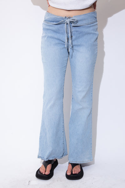 Light wash blue jeans in a flared leg style with tie around waist, light brown stitching and Tommy Hilfiger branding on the button and back waistline.