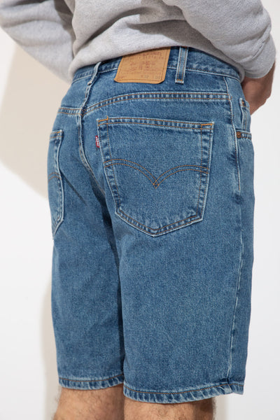 Mid-wash blue denim shorts in a midi-length with light brown stitching and Levi's branding on the button, domes, back waistline and back pocket.