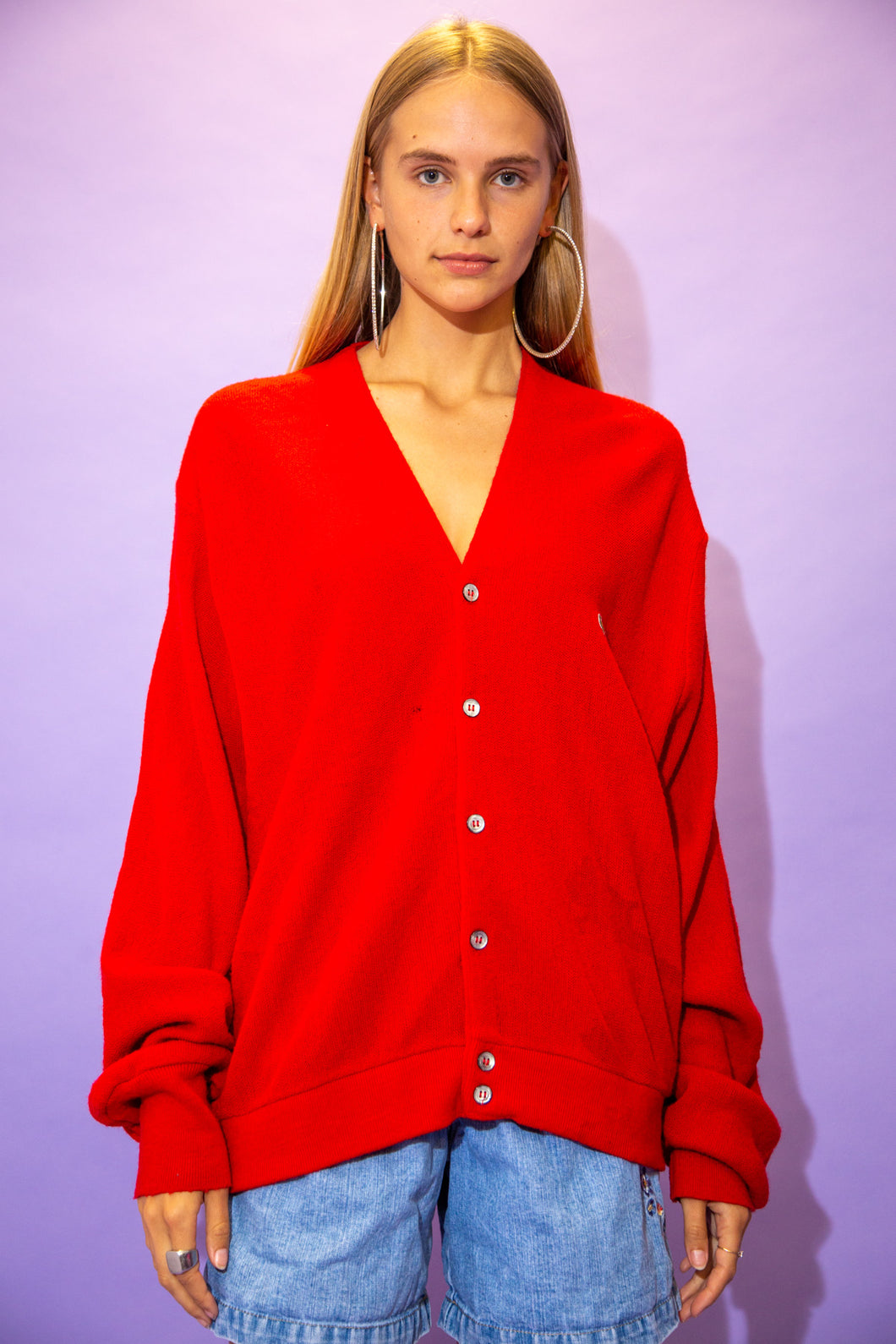 the model wears an oversized red lacoste cardigan