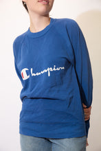 Load image into Gallery viewer, Blue in colour, this jumper has a white 'Champion' spell-out across the front with the brand's logo as the 'C'.