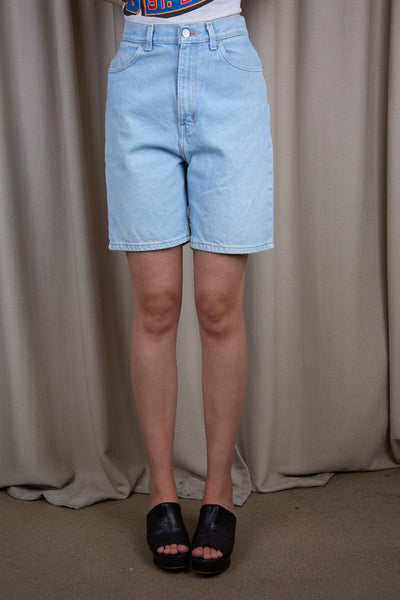 Light-wash denim shorts in a midi-length fit with light brown twitching and branding on the button and domes.