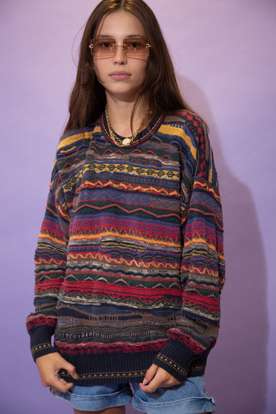 Horizontally patterned in a coogi style in red, navy blue, dark green, yellow and grey, this jumper is in a crew neck style in an oversized fit.