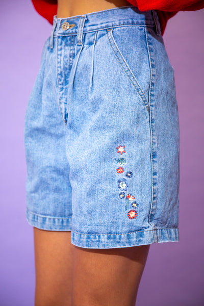 the model wears a pair of light washed blue denim shorts with an embroidered floral graphic on the left leg