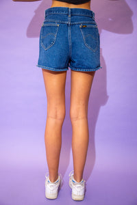 the model wears a dark blue washed pair of denim shorts