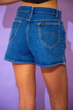Load image into Gallery viewer, the model wears a dark blue washed pair of denim shorts