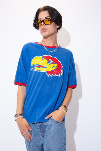 Blue in colour with a red rimmed neckline and sleeves, this tee has a large print of the Kansas Jayhawks mascot on the front.