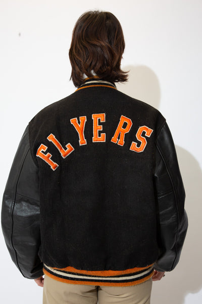 the model wears a black letterman jacket with flyers spell out