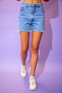 the model wears a pair of light washed blue denim shorts