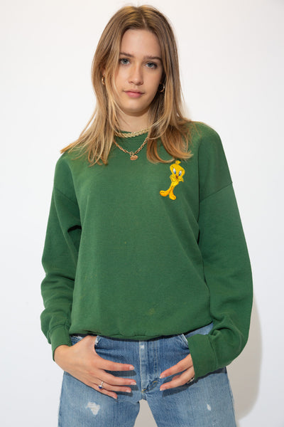 the model wears a deep green tweety sweater