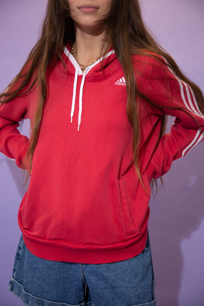 Pink in colour, this jumper has the signature three Adidas lines down the sleeves with a white rimmed hood, white draw strings and white Adidas branding on the left chest.