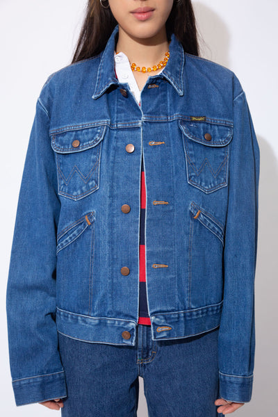 Dark wash blue denim jacket with brown stitching, double breast pockets, double side pockets and Wrangler branding on the buttons and left chest pocket.
