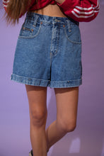 Load image into Gallery viewer, Mid-wash blue denim shorts with light brown stitching, folded rims and New York Jeans branding on the front pocket and button.