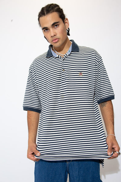 Horizontally striped in navy blue and white, this polo style tee has brown buttons and the iconic Tommy Hilfiger lion emblem on the left chest.