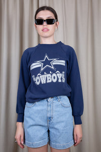 Navy blue in colour, this jumper has a white and grey 'Dallas Cowboy' spell-out across the front with the logo above.