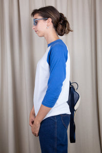 the model wears a blue and white raglan tee