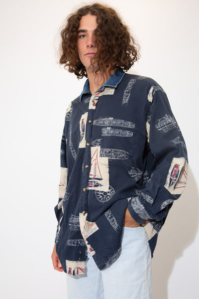 Sick navy blue button-up with a denim collar, a left chest pocket and an allover print of boat sketches and compasses.