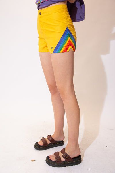 Yellow shorts in a thick board shorts material with rainbow edges and Ocean Pacific branding on the dome closure and left leg.