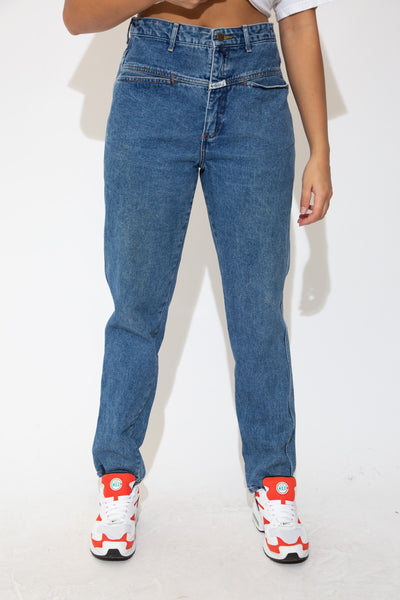 the model wears a mid blue wash pair of jeans