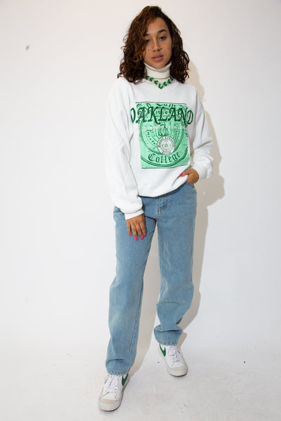 the model wears a white sweater with oakland college spell out
