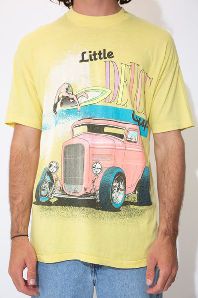 the model wears a yellow tee with a beach boys graphic